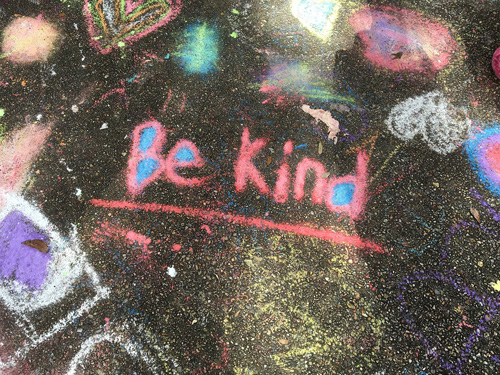 'Be Kind' written in bright chalk