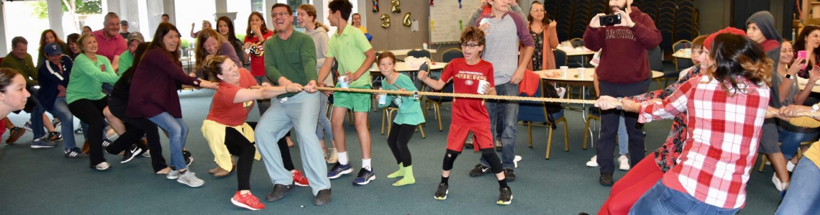 Adults playing tug-of-war against kids