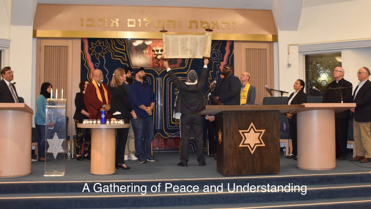 Interfaith service with a raised Torah